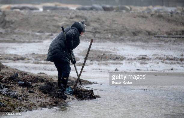 Scituate women uses a rake to clear a street drain on Kenneth Road on Apr 3 2020 after high winds and rain led to some flooding in Scituate MA