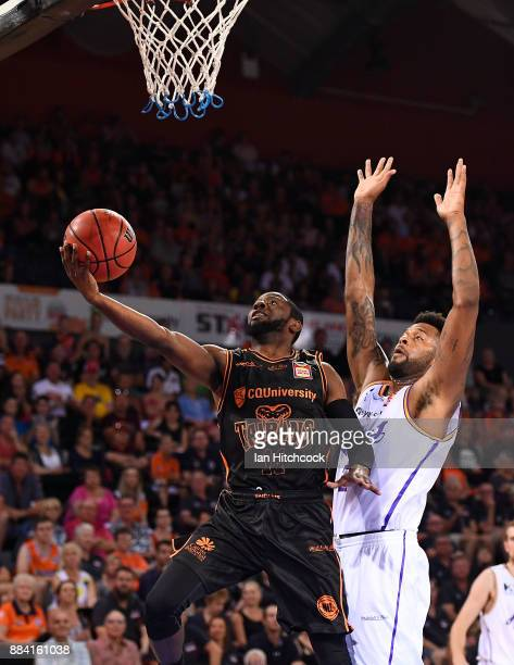 Scoochie Smith of the Taipans attempts a lay up past Jeremy Tyler of the Kings during the round eight NBL match between the Cairns Taipans and the...