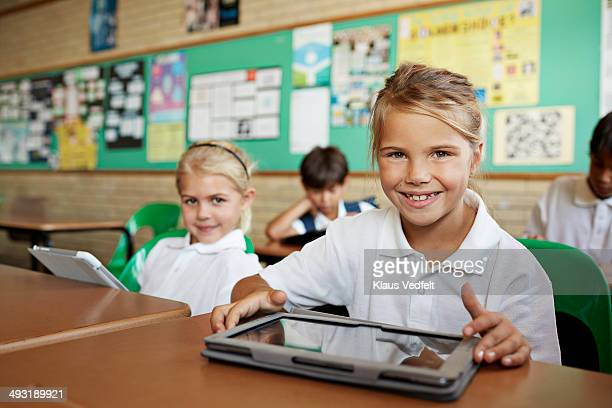 Scoolgirls with tablets, smiling to camera