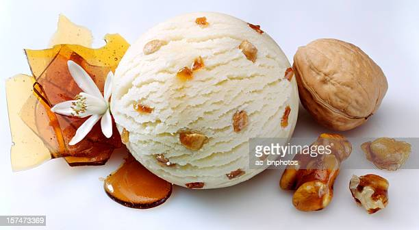 A scoop of vanilla ice cream with nuts and caramel