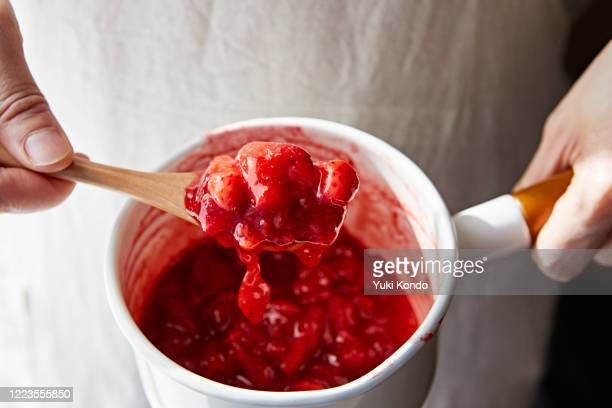 scoop the strawberry jam in the pan with a spoon - とろ火で煮た ストックフォトと画像