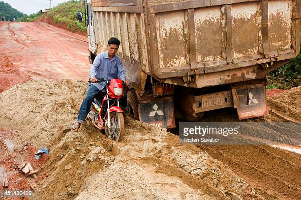 Scooter and truck stuck in mud on a soft section of the dirt road between Phonsavan and Paksan via Tathom. Some sections of this very muddy dirt road...