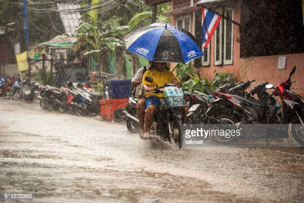 scooter driving at monsoon rain, koh tao, thailand - monsoon stock pictures, royalty-free photos & images