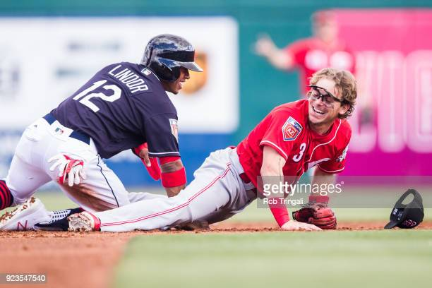 Scooter Gannett of the Cincinnati Reds shares a with Francisco Lindor of the Cleveland Indians during a Spring Training Game at Goodyear Ballpark on...
