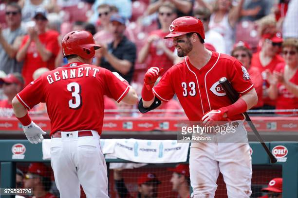 Scooter Gennett of the Cincinnati Reds celebrates with Jesse Winker after hitting a tworun home run to tie the game in the sixth inning against the...