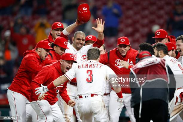 Scooter Gennett of the Cincinnati Reds celebrates with teammates after hitting a game winning tworun home run in the 12th inning against the Atlanta...