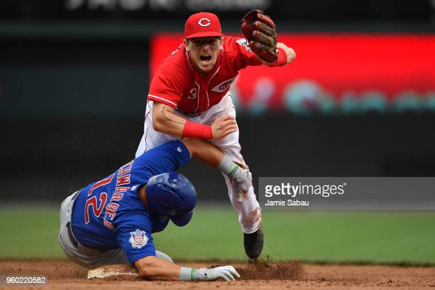Scooter Gennett of the Cincinnati Reds completes a double play in the seventh inning as Kyle Schwarber of the Chicago Cubs slides in to second base...