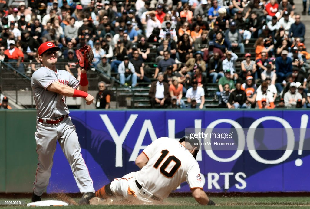 Scooter Gennett #3 of the Cincinnati Reds completes the double play throwing over the top of Evan Longoria #10 of the San Francisco Giants in the bottom of the seventh inning at AT&T Park on May 16, 2018 in San Francisco, California.