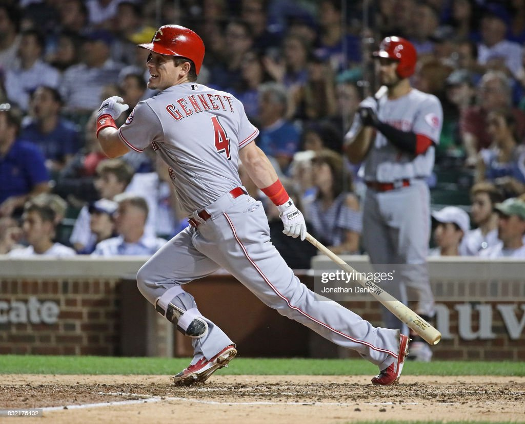 Scooter Gennett #4 of the Cincinnati Reds hits and RBI sacrifice fly in the 8th inning to score teammate Joy Votto against the Chicago Cubs at Wrigley Field on August 15, 2017 in Chicago, Illinois.