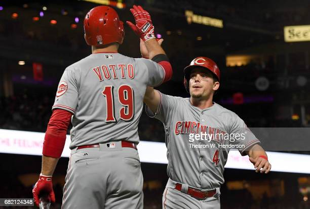 Scooter Gennett of the Cincinnati Reds is congratulated by Joey Votto after Gennett scored against the San Francisco Giants in the top of the eighth...