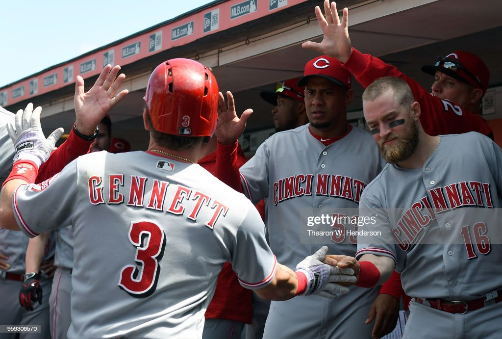 Scooter Gennett #3 of the Cincinnati Reds is congratulated by teammates Tucker Barnhart #16 and Wandy Peralta #53 after Gennett hit a solo home run against the San Francisco Giants in the top of the seventh inning at AT&T Park on May 16, 2018 in San Francisco, California.