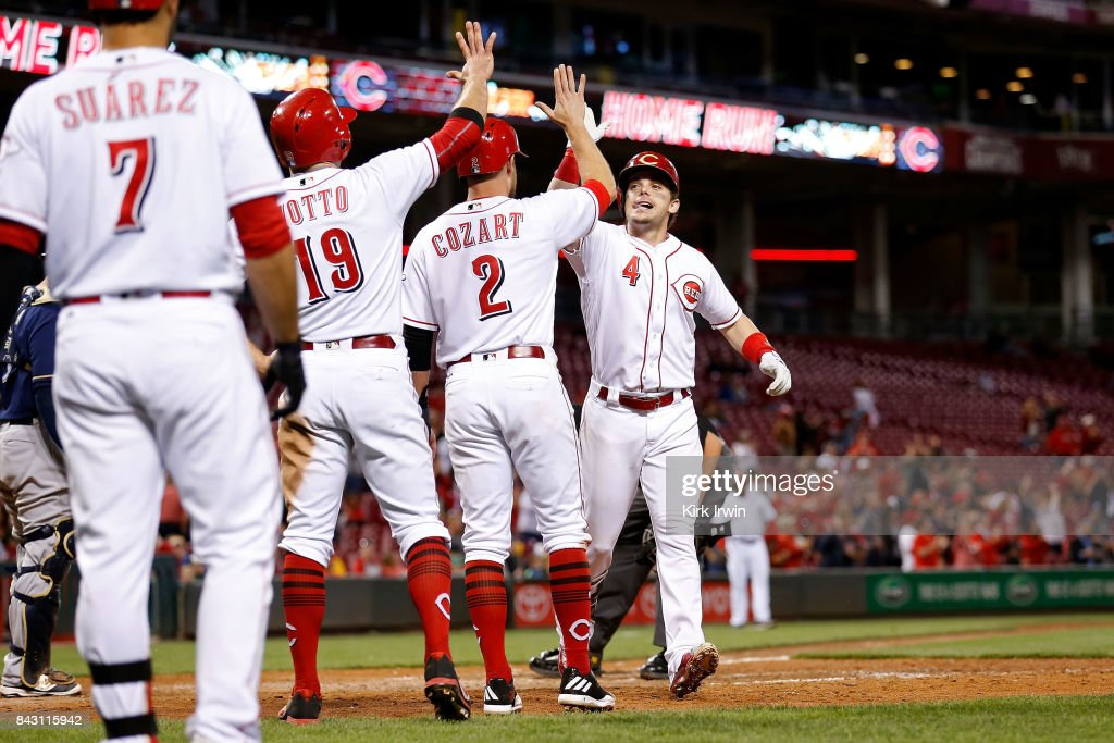 Scooter Gennett #4 of the Cincinnati Reds is congratulated by Zack Cozart #2 of the Cincinnati Reds and Joey Votto #19 of the Cincinnati Reds after hitting a three-run home run off of Wei-Chung Wang #58 of the Milwaukee Brewers during the seventh inning at Great American Ball Park on September 5, 2017 in Cincinnati, Ohio. Cincinnati defeated Milwuakee 9-3.