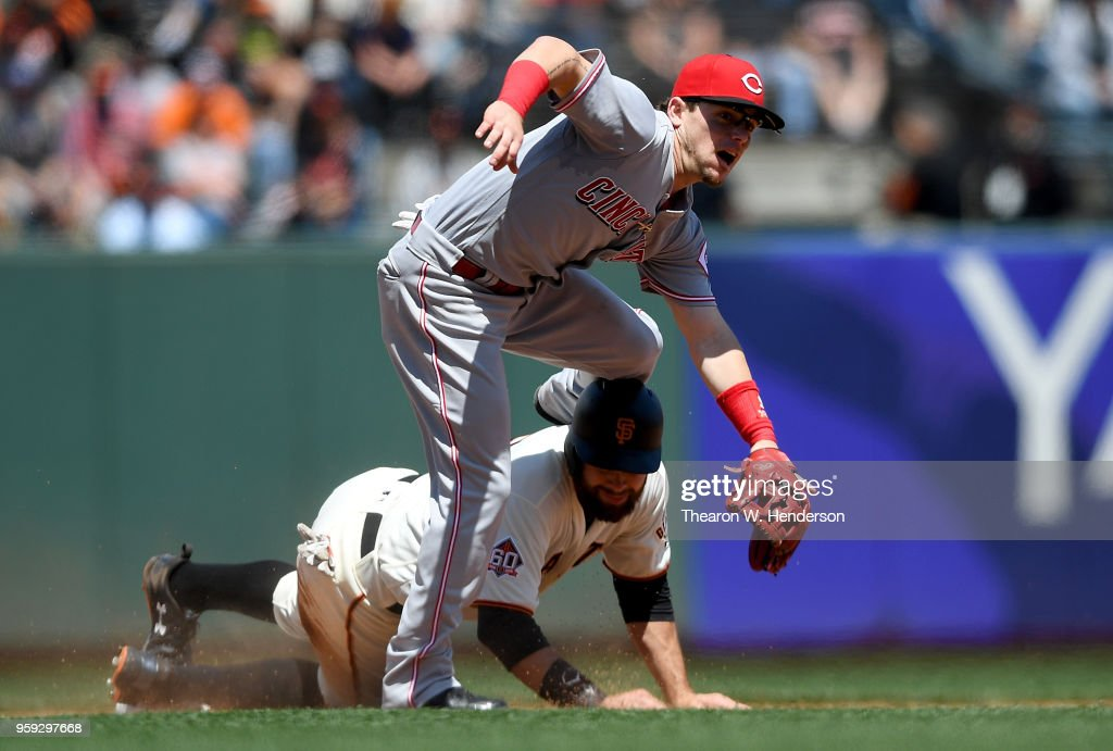 Scooter Gennett #3 of the Cincinnati Reds leaps over Brandon Belt #9 of the San Francisco Giants after getting his throw off to complete the douple play in the bottom of the fifth inning at AT&T Park on May 16, 2018 in San Francisco, California.