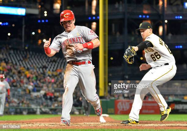 Scooter Gennett of the Cincinnati Reds scores on a wild pitch by Dovydas Neverauskas of the Pittsburgh Pirates in the eighth inning during the game...