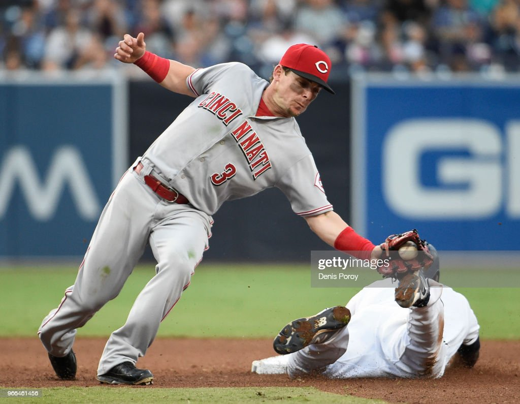 Scooter Gennett #3 of the Cincinnati Reds tags Jose Pirela #2 of the San Diego Padres on the foot to get the out as he tries to steal second base during the fifth inning of a baseball game at PETCO Park on June 2, 2018 in San Diego, California.