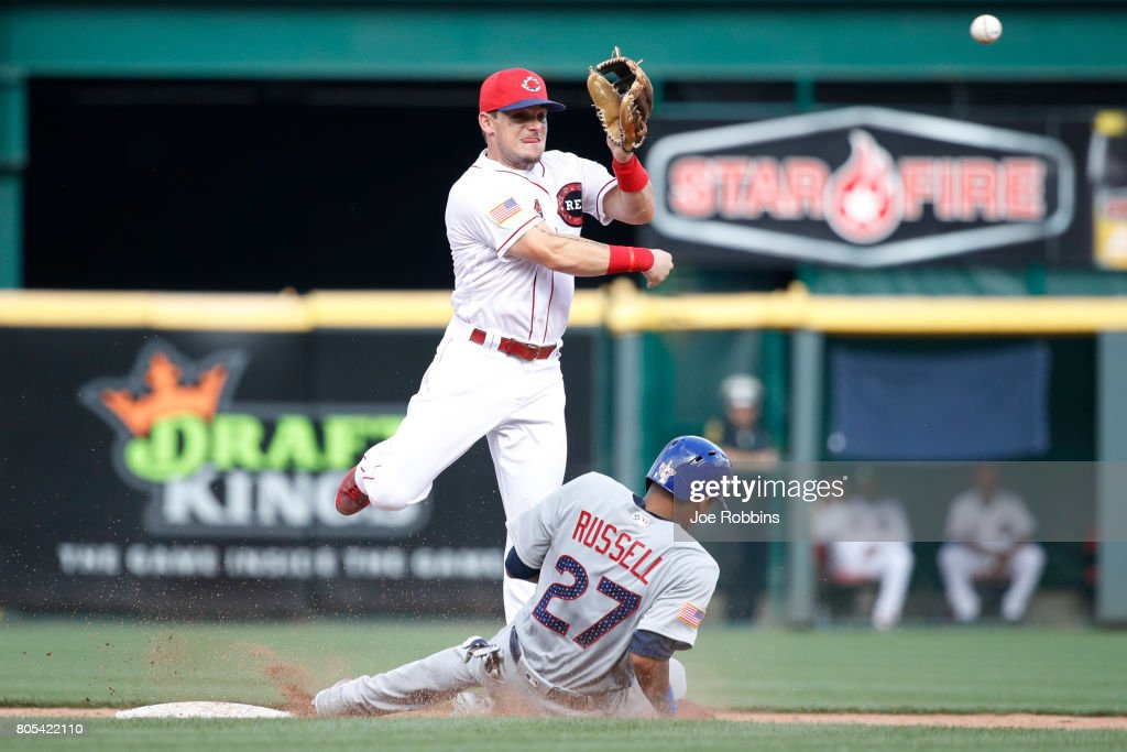 Scooter Gennett #4 of the Cincinnati Reds turns a double play over the sliding Addison Russell #27 of the Chicago Cubs in the sixth inning of a game at Great American Ball Park on July 1, 2017 in Cincinnati, Ohio. The Reds defeated the Cubs 5-3.