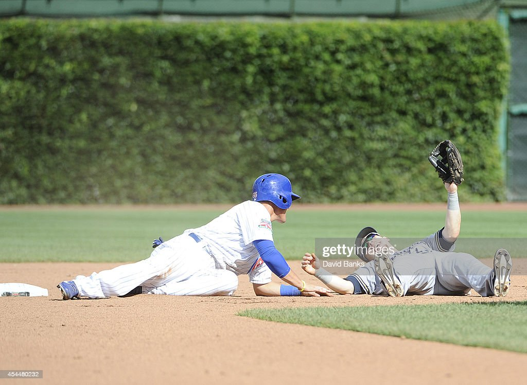Scooter Gennett (R) of the Milwaukee Brewers forces out Logan Watkins #45 of the Chicago Cubs during the seventh inning on September 1, 2014 at Wrigley Field in Chicago, Illinois.