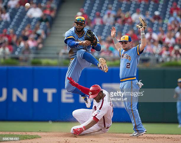 Scooter Gennett of the Milwaukee Brewers looks on as Jonathan Villar turns a double play against Jimmy Paredes of the Philadelphia Phillies in the...