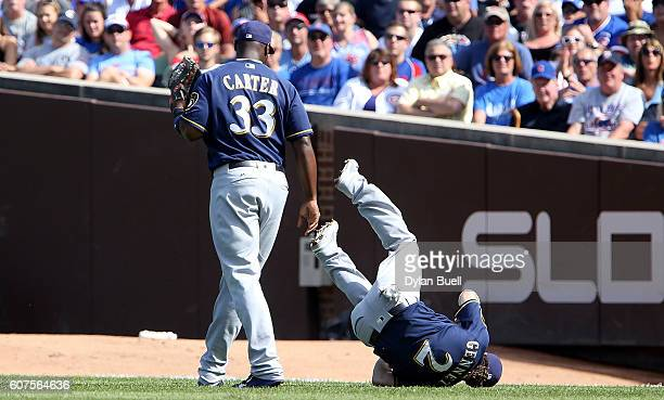 Scooter Gennett of the Milwaukee Brewers trips over Chris Carter in the third inning against the Chicago Cubs at Wrigley Field on September 18 2016...