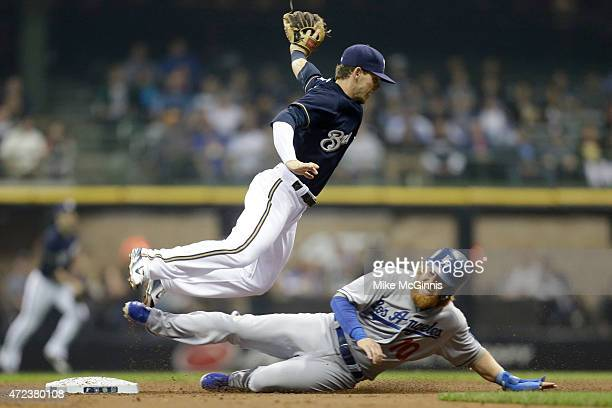 Scooter Gennett of the Milwaukee Brewers turns the double play as Justin Turner of the Los Angeles Dodgers slides into second base during the second...