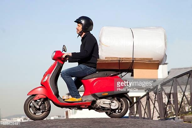 scooter laden with cargo - のりものに乗る ストックフォトと画像