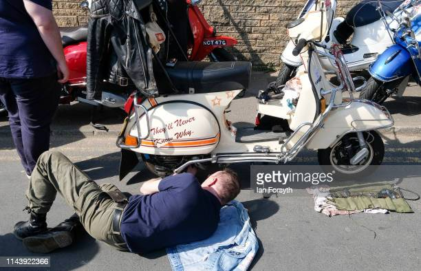 A scooter owner carries out maintenance on his bike as he takes part in the first day of the Easter National Scooter Rally on April 20 2019 in...