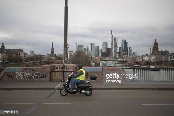 A scooter rider crosses a bridge spanning the River Main as skyscrapers stand in the financial district beyond in Frankfurt Germany on Thursday March...