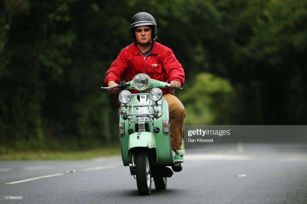 A scooter rider makes his way along a country lane during the the Isle of Wight International Scooter Rally on August 24, 2013 in Ryde, England. The annual event, which is organized by the British Scooter Rally Association and The VFM Scooter Collective, attracts around 6000 riders each year and has been running since 1980. The scooter in 1960's Britain was a fashion statement and the often heavily customized bikes, usually an Italian Vespa or Lambretta, became synonymous with the Mod scene. They provided an inexpensive mode of transport and escapism to an upwardly mobile youth at a time when public transportation stopped early. The Vespa was depicted on the cover of 'The Who's Quadrophenia album in 1973.