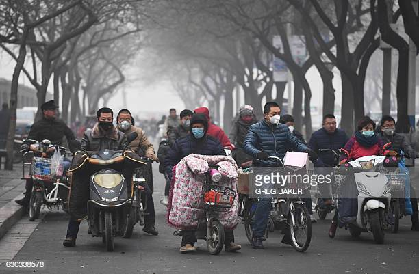 Scooter riders wait to cross a road on a heavily polluted day in Shijiazhuang in northern China's Hebei province on December 21 2016 China's...