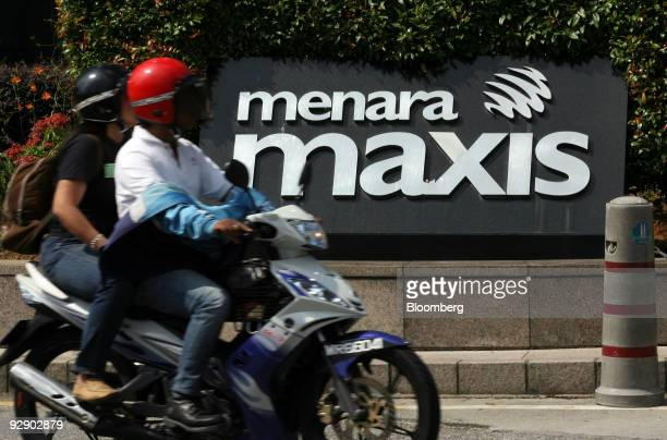 A scooter travels past the Maxis Bhd headquarters at Kuala Lumpur City Centre in Kuala Lumpur Malaysia on Saturday Nov 7 2009 Maxis Communications...