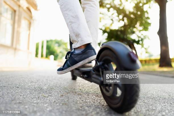 scooting around town - electric scooter stock pictures, royalty-free photos & images