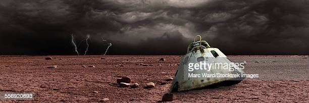 a scorched space capsule lies abandoned on a barren world. storm clouds and lightning are the background of a failed mission. - space capsule stock photos and pictures