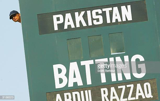 A score board worker watches the match during day 3 of the 1st Test Match between Pakistan and India at Multan Stadium on March 30 2004 in Multan...