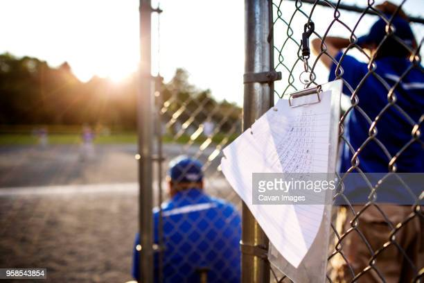 Score card hanging on fence with coach in background