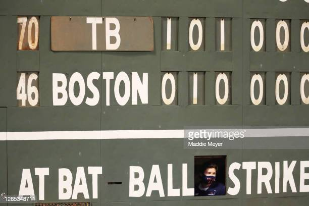 Scoreboard attendant watches the game between the Boston Red Sox and the Tampa Bay Rays from the Green Monster during the ninth inning at Fenway Park...