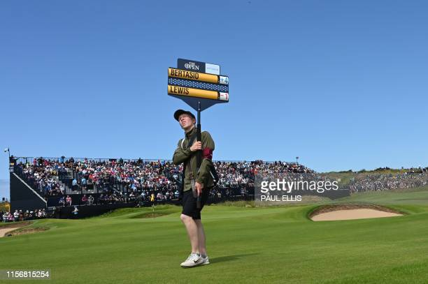 A scoreboard carrier walks past the 13th green during the third round of the British Open golf Championships at Royal Portrush golf club in Northern...
