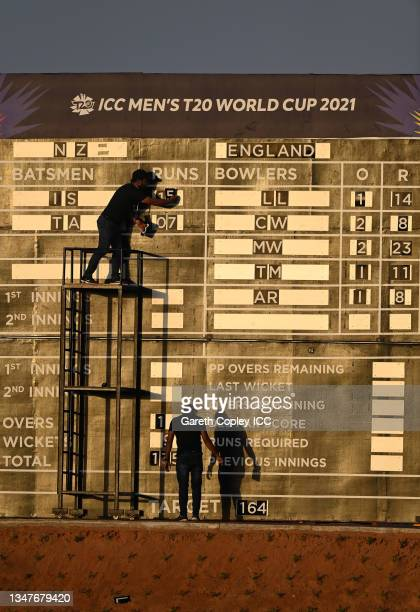 Scoreboard operators change the score during the England and New Zealand warm Up Match prior to the ICC Men's T20 World Cup at on October 20, 2021 in...