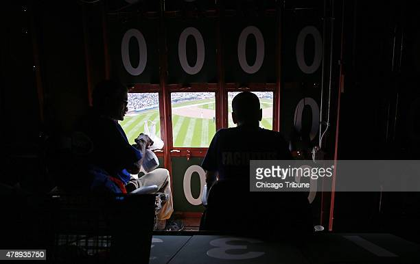 Scoreboard operators Freddy Washington left and Brian Helmus watch game action on the field while working inside the original Wrigley Field...