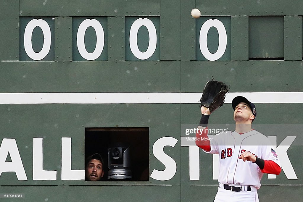 A scorekeeper inside the Green Monster watches Andrew Benintendi #40 of the Boston Red Sox catche a fly ball hit by Josh Donaldson #20 of the Toronto Blue Jays as during the fifth inning at Fenway Park on October 2, 2016 in Boston, Massachusetts.