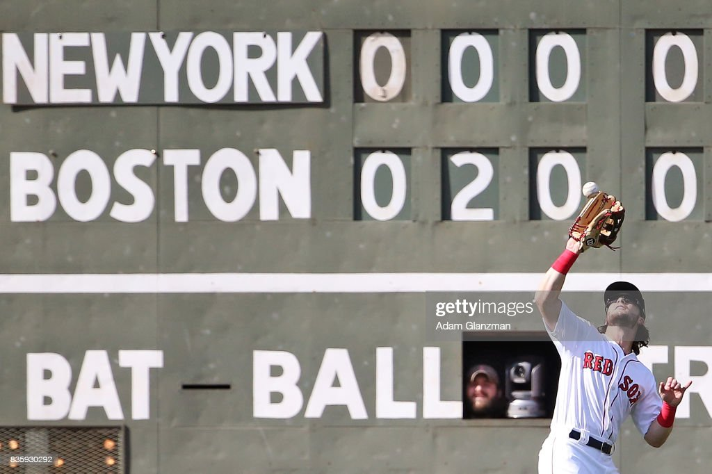 A scorekeeper pops his head out of the Green Mosnter while Andrew Benintendi #16 of the Boston Red Sox makes a catch in the sixth inning of a game against the New York Yankees at Fenway Park on August 20, 2017 in Boston, Massachusetts.