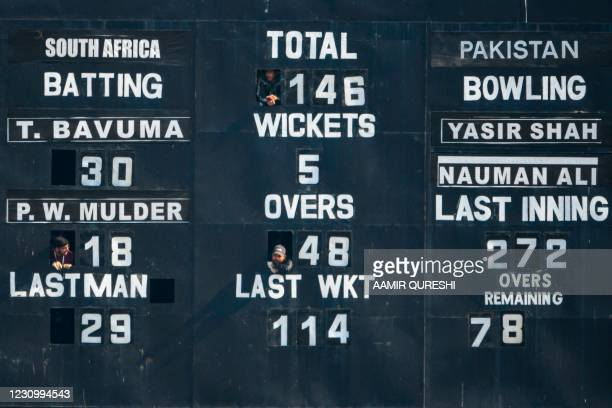 Scorekeepers peer out of small windows of a scoreboard during the third day of the second Test cricket match between Pakistan and South Africa at the...