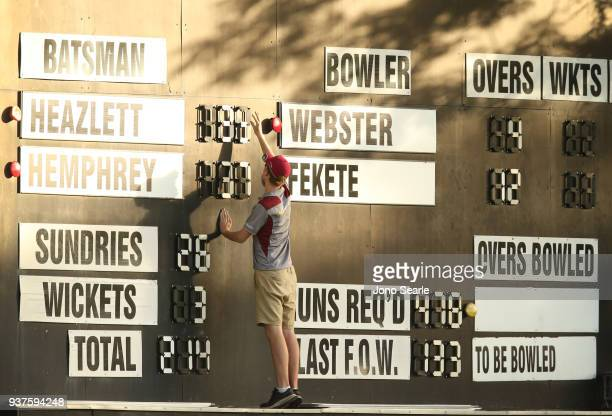 A scorer adjust the score board during day three of the Sheffield Shield final match between Queensland and Tasmania at Allan Border Field on March...