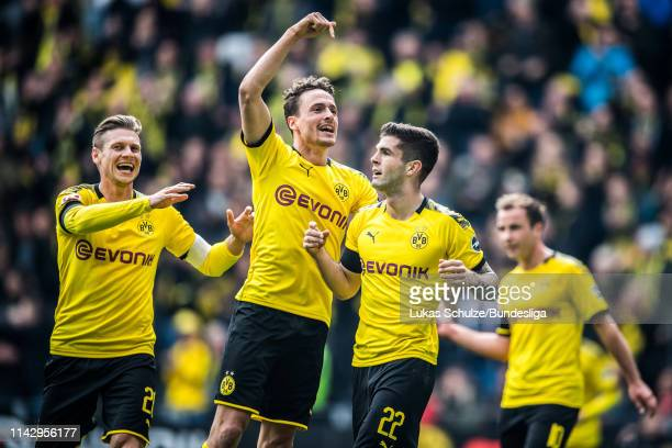 Scorer Christian Pulisic of Dortmund celebrates his team's first goal with Thomas Delaney and Lukasz Piszczek of Dortmund during the Bundesliga match...