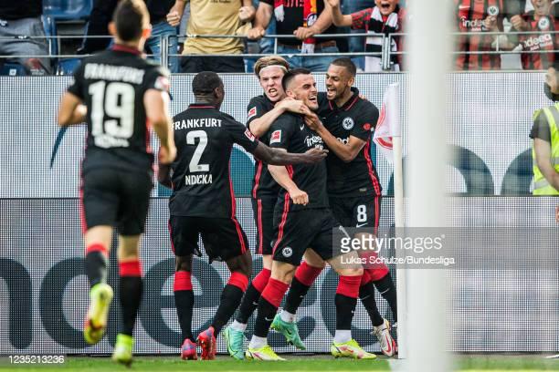 Scorer Filip Kostic celebrates his teams first goal with Evan Ndicka , Jens Petter Hauge and Djibril Sow during the Bundesliga match between...