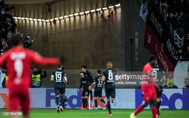 Scorer Filip Kostic of Frankfurt celebrates his team's fourth goal with team mates during the UEFA Europa League Round of 32 first leg match between...