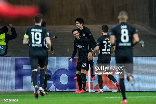 Scorer Filip Kostic of Frankfurt celebrates his team's fourth goal with Daichi Kamada and team mates during the UEFA Europa League Round of 32 first...