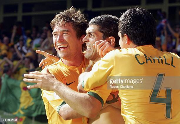 Scorer of Australia's third goal John Aloisi is congratulated by teammates Harry Kewell and Tim Cahill during the FIFA World Cup Germany 2006 Group F...