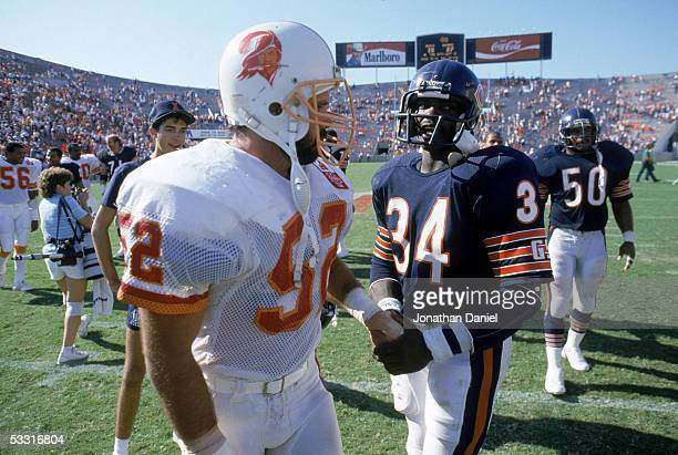 Scot Brantley of the Tampa Bay Buccaneers meets with Walter Payton of the Chicago Bears following the game at Tampa Stadium on October 6 1985 in...