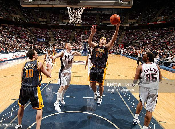 Scot Pollard of the Indiana Pacers goes up for a shot against Brian Scalabrine and Jason Collins of the New Jersey Nets on March 22 2005 at the...
