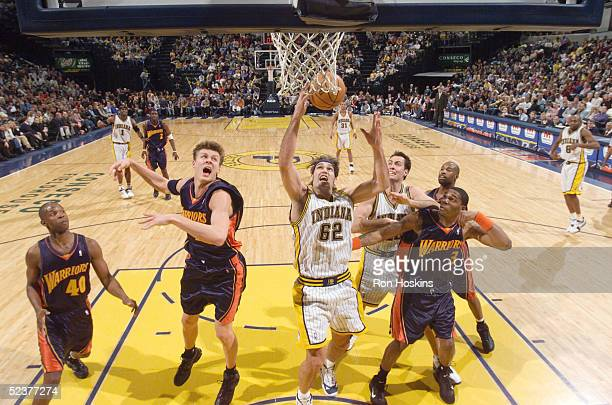 Scot Pollard of the Indiana Pacers rebounds over Andris Biedrins and Rodney White of the Golden State Warriors on March 11, 2005 at Conseco...